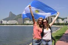 Sportfreunde, welche die argentinische Flagge in Rio de Janeiro mit Christus der Erlöser im Hintergrund halten Stockfotografie