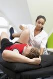 Sportfysioterapeut Treating Male Client Arkivbilder