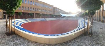 Sportground moderne avec les sièges bleus sur la cour entre le bâtiment contre le soleil Photos stock