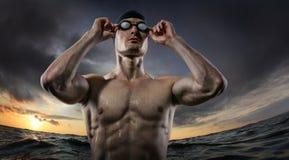 Sporthintergr?nde Junge athletische Schwimmerstellung nahe dem Sonnenuntergangfluß stockfoto