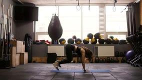 Sportief aantrekkelijk donkerbruin meisje die vette het branden reeks oefeningen in de gymnastiek op vloermat doen Geschiktheid e stock video