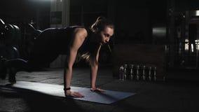 Sportief aantrekkelijk meisje die Lopende Plank doen Gymnastiek De mens van de geschiktheid training Avondoefeningen Het concept  stock videobeelden