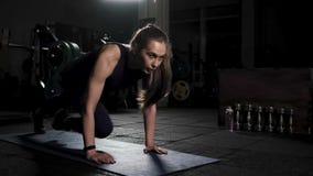 Sportief aantrekkelijk meisje die Lopende Plank doen Gymnastiek De mens van de geschiktheid training Avondoefeningen om de spiere stock videobeelden