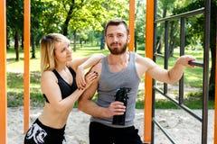 Sportief blondemeisje en gebaarde mens die na training rusten trainin royalty-vrije stock afbeelding