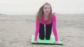 Sportief jong mooi meisje die oefeningen op het zand doen Mening van voorzijde stock videobeelden