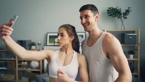 Sportief jong paar die selfie samen thuis het stellen voor smartphonecamera nemen stock video