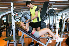 Sportief jong paar die spieroefening in gymnastiek doen stock foto's
