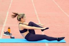 Sportief meisje die been uitrekkende zitting op een geschiktheidsmat doen bij het stadion Groep en individuele sportactiviteiten  royalty-vrije stock afbeeldingen