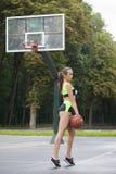 Sportief meisje die zich met een basketbalbal bevinden Stock Foto
