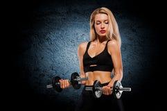 Sportief meisje met het ideale cijfer stellen in de studio met dum Stock Foto's