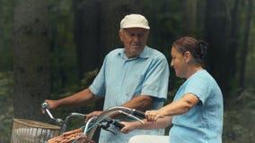 Sportief oud paar met fietsenbesprekingen in park stock video