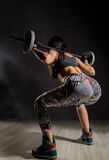Sportief sexy meisje met barbell op een donkere achtergrond Atleet die oefeningen in de gymnastiek doen Royalty-vrije Stock Afbeelding