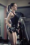 Sportieve aantrekkelijke vrouw in de gymnastiek met oefeningsmateriaal Royalty-vrije Stock Foto