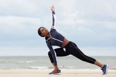 Sportieve Afrikaanse Amerikaanse vrouw het uitrekken zich spieren bij het strand royalty-vrije stock afbeelding
