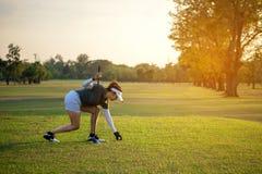 Sportieve Aziatische golfspelervrouw die golfbal op T-stuk met club in golfcursus zetten op zonnige dag voor gezonde sport royalty-vrije stock foto's