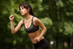 Sportieve donkerbruine vrouwenjogging in park Stock Afbeelding