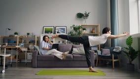 Sportieve echtgenoot die yoga doen terwijl meisje die op mobiele laptop van de telefoonholding spreken stock video