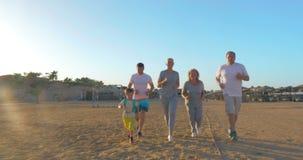 Sportieve familie die op het strand lopen stock videobeelden