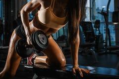 Sportieve gelooide vrouw met perfecte vorm opheffende domoren in de gymnastiek Sluit omhoog stock foto