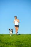 Sportieve gelukkige vrouw die met hond lopen stock foto