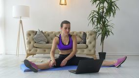 Sportieve geschikte vrouw met laptop het uitrekken zich spieren stock videobeelden
