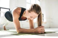 Sportieve glimlachende vrouwelijke atleet die abs oefening in witte zonnige gymnastiek doen royalty-vrije stock foto