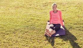 Sportieve hogere vrouwenzitting op oudoors van een yogamat royalty-vrije stock fotografie