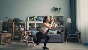 Sportieve jonge dame die op één been hurken die thuis alleen in flat uitoefenen stock video