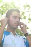 Sportieve jonge mens die zijn oortelefoon aanpassen tijdens jogging Royalty-vrije Stock Foto