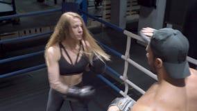 Sportieve jonge vrouw in bokshandschoenenponsen haar mannelijke instructeur, die in dozen doende schopstootkussens voor beschermi stock videobeelden