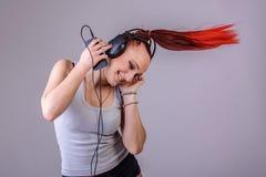 Sportieve jonge vrouw die aan muziek dansen Stock Foto's