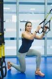 Sportieve jonge vrouw die oefening doen bij de gymnastiek Stock Foto's