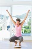 Sportieve jonge vrouw die op het wegen schaal in gymnastiek buigen Stock Fotografie