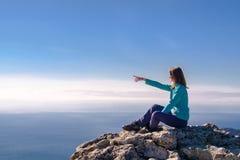 Sportieve jonge vrouwenzitting in een rotsachtige bovenkant van de berg stock foto's