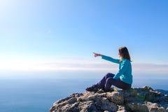 Sportieve jonge vrouwenzitting in een rotsachtige bovenkant van de berg tegen het blauw van hemel en overzees stock foto's