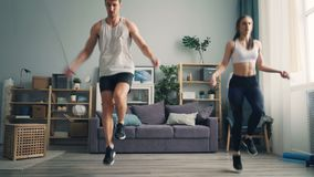 Sportieve jongerenman en vrouw die sportentouwtjespringen samen in vlakte doen stock video