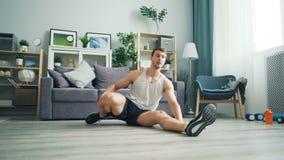Sportieve kerel uitrekkende zitting op vloer die aan been buigen die flexibiliteit ontwikkelen stock video