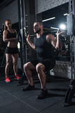 Sportieve mens die barbell met trainer dichtbij langs bij gymnastiek opheffen Royalty-vrije Stock Afbeelding