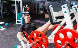 Sportieve mens die in sportkleding op een machine uitwerken stock afbeelding