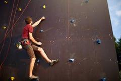 Sportieve mens het praktizeren bergbeklimming in gymnastiek op kunstmatige rots opleidingsmuur in openlucht De jongelui talanted  royalty-vrije stock fotografie