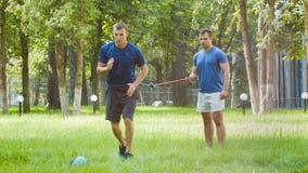 Sportieve mens twee of instructeurs die gymnastiek- oefening doen openlucht stock footage