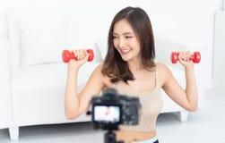 Sportieve mooie Aziatische vrouw die blogger een video registreren die thuis geschikt uitoefenen te blijven stock foto's