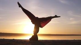 Sportieve mooie jonge gevorderde yogavrouw die in Sirsasana zich in openlucht op het strand bevinden Mooie zonsondergang, silhoue stock videobeelden