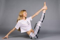 Sportieve mooie jonge vrouw het praktizeren yoga, uitwerkend dragend grijze en witte sportkleding, studio, volledige lengte Royalty-vrije Stock Fotografie
