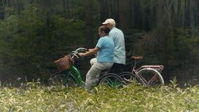 Sportieve oude mensenritten op fietsen in het park stock videobeelden