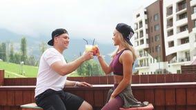 Sportieve paarzitting in een koffie die van verse dranken na intensieve training genieten stock videobeelden