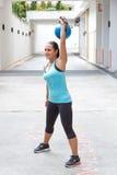 Sportieve Spaanse vrouw die in blauw blauwe kettlebell voor snatch routine in openlucht opheffen stock fotografie
