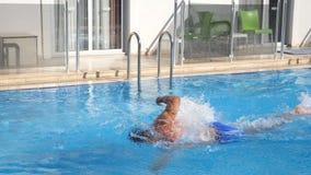 Sportieve spiermens die in pool zwemmen Jonge kerel die over het bassin van hotel op zonnige dag drijven De zomervakantie of stock video