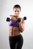 Sportieve spiervrouw met twee domoren Stock Fotografie