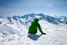 Sportieve vrouw die aan sneeuwbergen kijken Royalty-vrije Stock Foto's